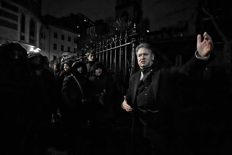 Richard Jones with a ghost walk group by a church railing.